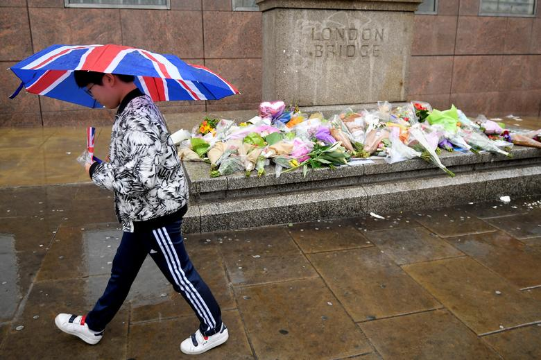 A pedestrian carrying an umbrella walks past floral tributes to the victims of the recent attack at London Bridge and Borough Market, in central London, Britain June 6, 2017.  REUTERS/Toby Melville