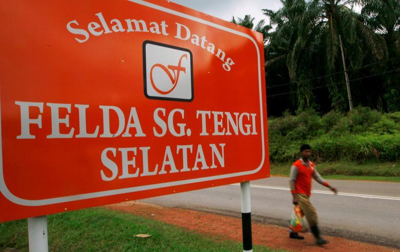 FILE PHOTO: A man walks past a welcome signboard outside the Federal Land Development Authority (FELDA) Sungai Tengi Selatan palm oil plantation in Hulu Selangor,  north of Kuala Lumpur February 22, 2012.   REUTERS/Samsul Said/File Photo