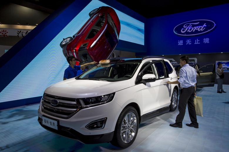 FILE PHOTO: A visitor (R) gets in a Ford Edge SUV at the 13th China (Guangzhou) International Automobile Exhibition in Guangzhou, China November 20, 2015.   REUTERS/Tyrone Siu/File Photo