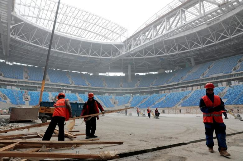 FILE PHOTO: Labourers work at a new stadium under construction on Krestovsky Island, known as Zenit Arena, that will host 2017 FIFA Confederations Cup and 2018 FIFA World Cup matches, in St. Petersburg, Russia, October 3, 2016.  REUTERS/Pawel Kopczynski