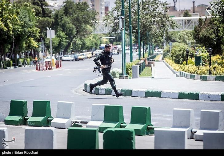 A member of Iranian forces runs during an attack on the Iranian parliament in central Tehran, Iran, June 7, 2017. Tasnim News Agency/Handout via REUTERS