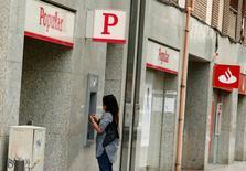 Mulher usa caixa eletrônico do Banco Popular, ao lado de um escritório do Santander, em Barcelona. 07/06/2017 REUTERS/Albert Gea