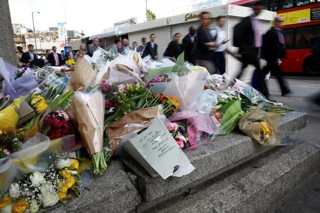 Commuters walk past floral tributes near the scene of the recent attack at London Bridge and Borough Market in central London, Britain June 7, 2017. REUTERS/Stefan Wermuth
