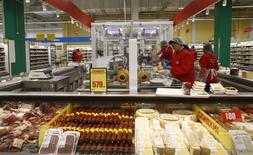 Employees prepare cheese at a grocery store which is the 100th store of French retail group Auchan opened in the country, in Moscow, Russia, December 13, 2016.  REUTERS/Maxim Shemetov