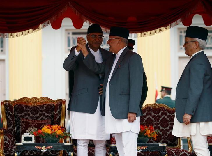 Newly elected Nepalese Prime Minister Sher Bahadur Deuba (L) holds the hand of former Prime Minister Khadga Prasad Sharma Oli as he greets him after swearing-in ceremony at the presidential building in Kathmandu, Nepal June 7, 2017. REUTER/Navesh Chitrakar