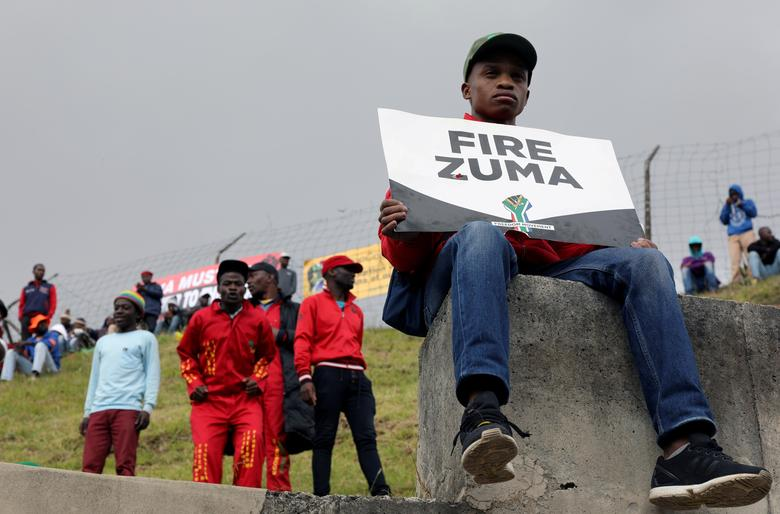 FILE PHOTO: FILE PHOTO: Supporters of various opposition parties hold placards calling for the removal of President Jacob Zuma outside the Constitutional Court in Johannesburg, South Africa, May 15, 2017. REUTERS/Marius Bosch/File Photo