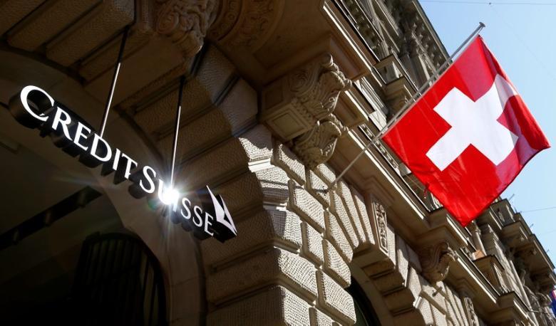 Switzerland's national flag flies beside the logo of Swiss bank Credit Suisse in Zurich, Switzerland April 24, 2017.  REUTERS/Arnd Wiegmann