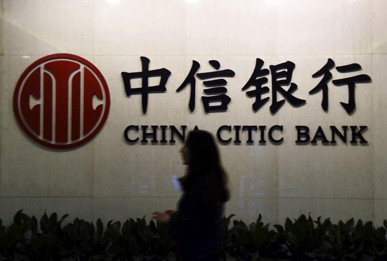 A customer walks past the company logo of China CITIC Bank, at a branch in Hangzhou, Zhejiang province, China, November 18, 2015. REUTERS/China Daily/File Photo