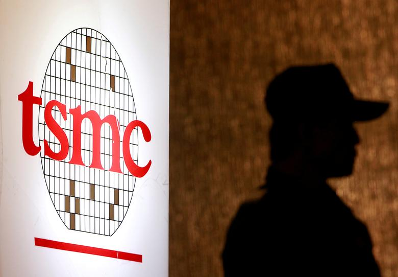 FILE PHOTO - A security staff member stands near the logo of Taiwan Semiconductor Manufacturing Co. Ltd (TSMC) during an investor conference in Taipei, Taiwan July 16, 2014.  REUTERS/Pichi Chuang/File Photo