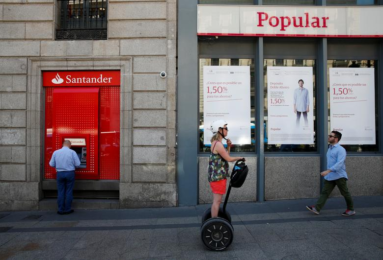 A man uses a cash dispenser at a branch of Spain's biggest bank Santander next to a Banco Popular branch on the same day Santander announced that it would buy struggling rival Banco Popular for a nominal one euro after European authorities determined the lender was on the verge of insolvency, in Madrid, Spain June 7, 2017. REUTERS/Juan Medina
