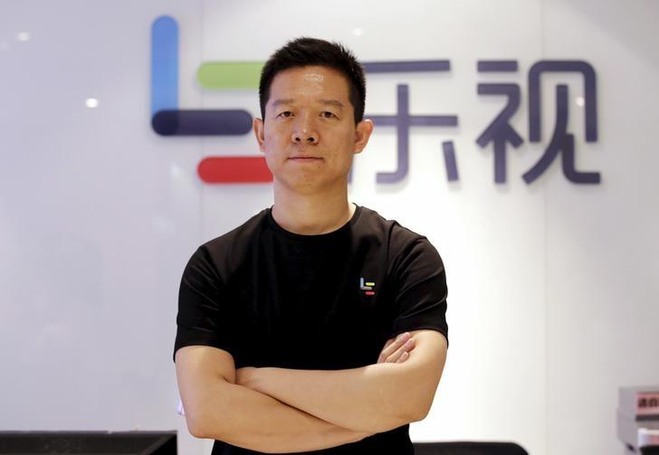 Jia Yueting, co-founder and head of Le Holdings Co Ltd, also known as LeEco and formerly as LeTV, poses for a photo in front of a logo of his company after a Reuters interview at LeEco headquarters in Beijing, China, picture taken April 22, 2016. To match Insight AUTOSHOW-BEIJING/CHINA-LEECO     REUTERS/Jason Lee