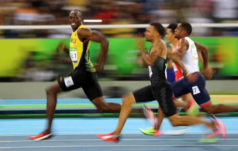 2016 Rio Olympics - Athletics - Semifinal - Men's 100m Semifinals - Olympic Stadium - Rio de Janeiro, Brazil - 14/08/2016. Usain Bolt (JAM) of Jamaica looks at Andre De Grasse (CAN) of Canada as they compete.  REUTERS/Kai Pfaffenbach