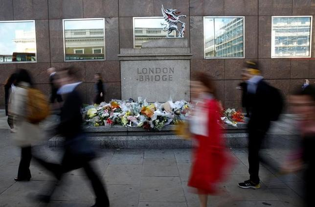 Commuters walk past floral tributes to the victims of the recent attack at London Bridge and Borough Market in central London, Britain June 7, 2017. REUTERS/Stefan Wermuth