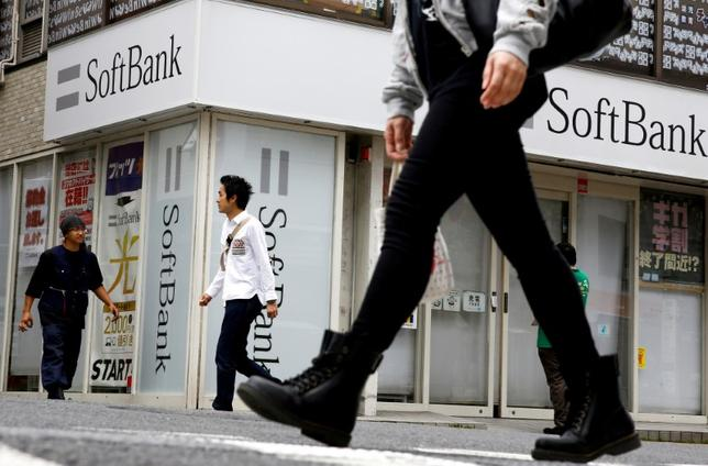 FILE PHOTO: People walk past a retail shop of the SoftBank telecommunications company in Tokyo, Japan, May 10, 2016. REUTERS/Thomas Peter/File Photo