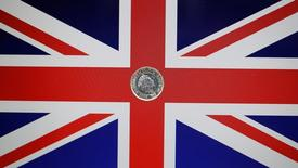 A one pound coin lies on a Union Flag in Loughborough, Britain May 3, 2017. REUTERS/Darren Staples