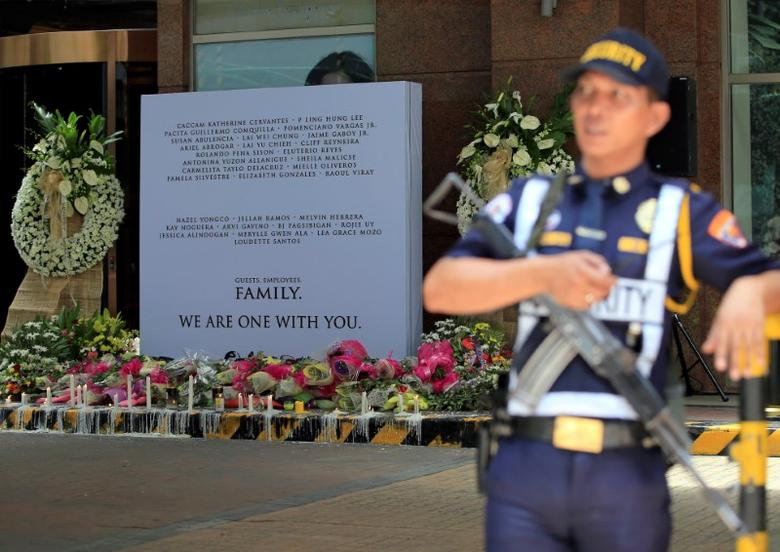 A security guard stands on attention in front of a memorial for those killed in a casino fire caused by a gunman at Resorts World in Pasay City, Metro Manila, Philippines June 4, 2017. REUTERS/Romeo Ranoco