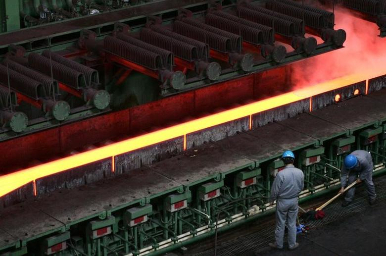 Chinese employees work near a machine for hot-rolled steel at the Baosteel factory in Shanghai February 25, 2005. REUTERS/Claro Cortes IV