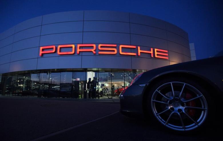 FILE PHOTO: An illuminated Porsche logo is pictured on a building of a Porsche retail centre in Niederwangen, Switzerland, March 9, 2012.  REUTERS/Michael Buholzer/File Photo