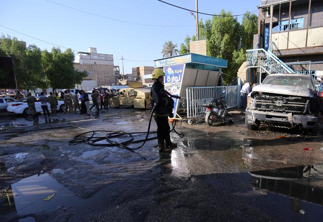 A firefighter hoses down a street after a suicide bomb attack in the city of Kerbala, Iraq June 9, 2017.  REUTERS/Stringer