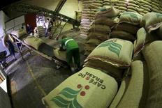 Trabalhador coloca sacas de café para exportação em esteira em armazém de café em Santos, no Brasil 10/12/2015 REUTERS/Paulo Whitaker