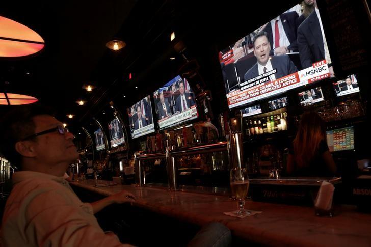 FILE PHOTO: A man watches a television showing former FBI director James Comey's testimony before the Senate Intelligence Committee, in Tonic bar in New York City, U.S., June 8, 2017. REUTERS/Joe Penney/File Photo