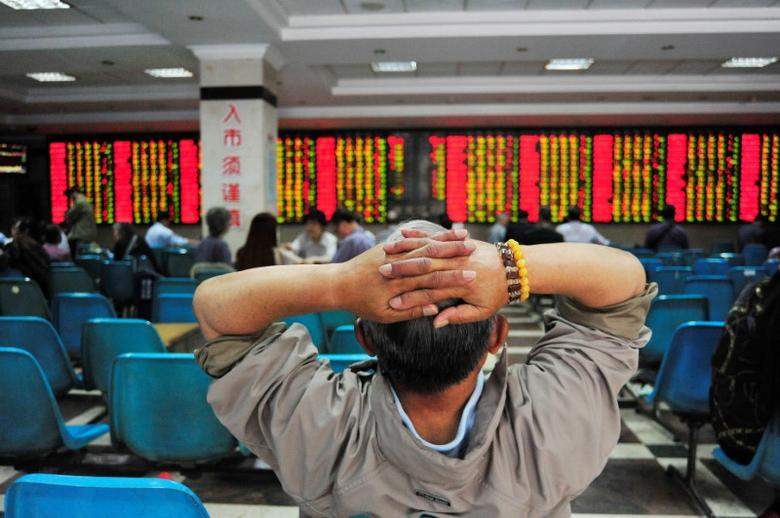 An investor looks at an electronic board showing stock information at a brokerage house in Nanjing, China May 24, 2017. REUTERS/Stringer