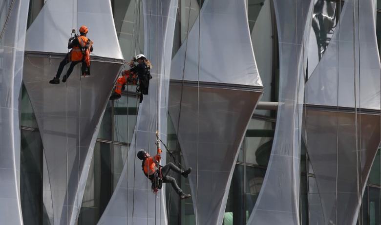 Construction workers climb a new building in the Nine Elms area of London, Britain April 11, 2017. REUTERS/Neil Hall