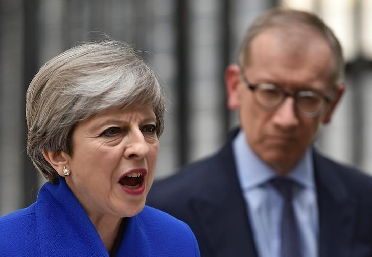 Britain's Prime Minister Theresa May addresses the country from Downing Street the day after the U.K.'s June 8 election. Her husband Philip looks on. REUTERS/Hannah Mckay