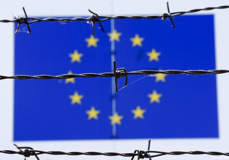 FILE PHOTO: A barbed wire is seen in front of a European Union flag at an immigration reception centre in Bicske, Hungary June 25, 2015.  REUTERS/Laszlo Balogh