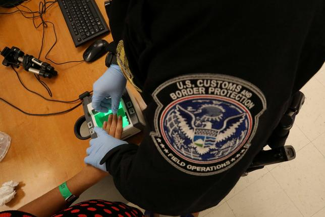 FILE PHOTO: A woman who is seeking asylum has her fingerprints taken by a U.S. Customs and Border patrol officer at a pedestrian port of entry from Mexico to the United States, in McAllen, Texas, U.S., May 10, 2017. REUTERS/Carlos Barria/File Picture