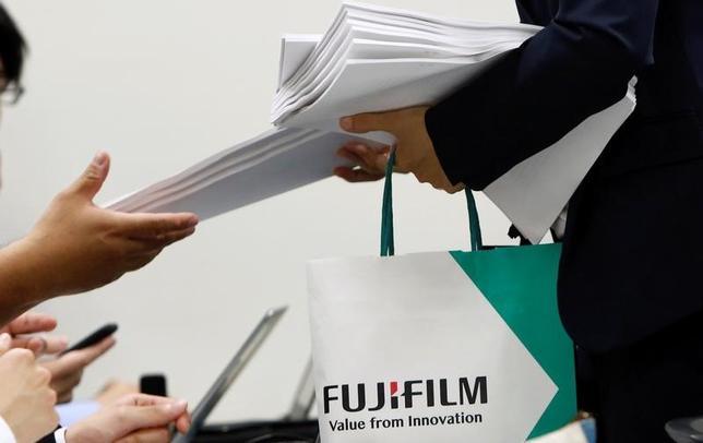 6月13日、富士フイルムホールディングス株が反落。同社は12日、子会社富士ゼロックスのニュージーランドとオーストラリアの販売子会社で不適切な会計処理が行われたことにより、2010年度から15年度までの6年間の過年度修正額が281億円に上ると発表した。写真は、決算資料を配る富士フイルムの社員。都内で12日撮影(2017年 ロイター/Kim Kyung-Hoon)