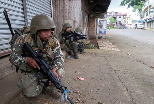 6月13日、フィリピン軍幹部は、過激派組織「イスラム国」(IS)系武装勢力が南部ミンダナオ島のマラウィ市の約20%をなお支配下に置いていると明らかにした。写真はマラウィ市を警備する警察と兵士たち。7日撮影(2017年 ロイター)
