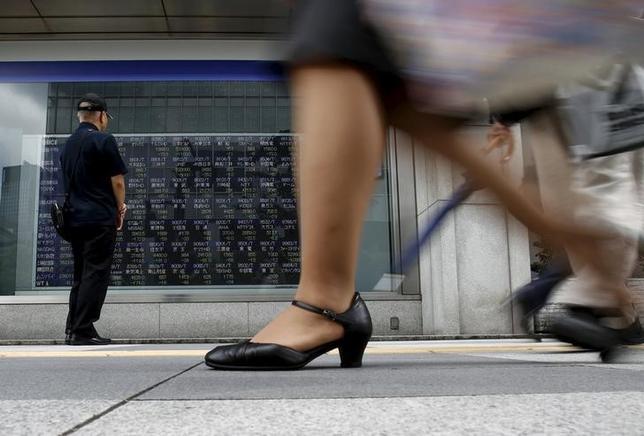 6月14日、寄り付きの東京株式市場で、日経平均は前日比75円81銭高の1万9974円56銭となり、反発して始まった。写真は株価ボードを眺める男性、都内で2015年8月撮影(2017年 ロイター/Yuya Shino)