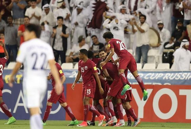 6月13日、サッカーのワールドカップ(W杯)アジア最終予選はA組の2試合を行い、韓国は敵地でカタールに2─3で敗れた。カタールは勝ち点7の5位となり、韓国は同13の2位にとどまった。写真はゴールを喜ぶカタールの選手たち(2017年ロイター/Ibraheem Al Omari)
