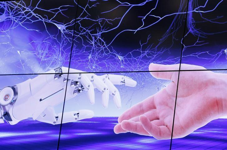 """2017年6月7日,瑞士日内瓦,""""人工智能造福人类全球峰会""""召开,大屏幕上显示机器人的手与人类的手彼此靠近。REUTERS/Denis Balibouse"""