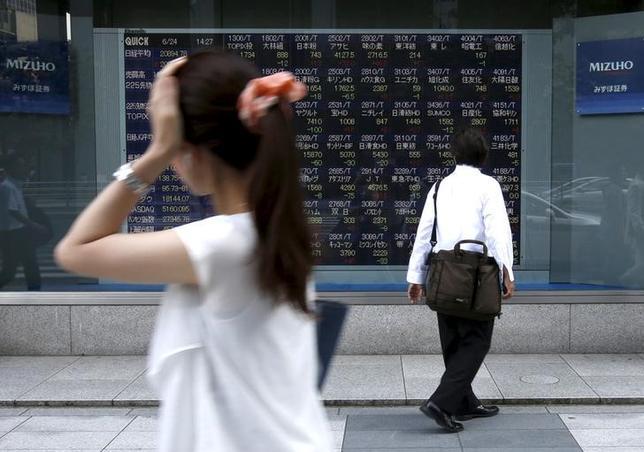 6月14日、前場の東京株式市場で、日経平均株価は前日比20円34銭高の1万9919円09銭となり小反発した。写真は株価ボードを眺める男性、都内で2015年6月撮影(2017年 ロイター/Issei Kato)