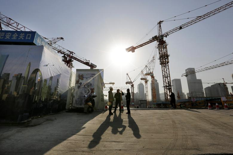FILE PHOTO: Workers chat outside a construction site in Beijing's central business district, December 29, 2014.   REUTERS/Jason Lee/File Photo