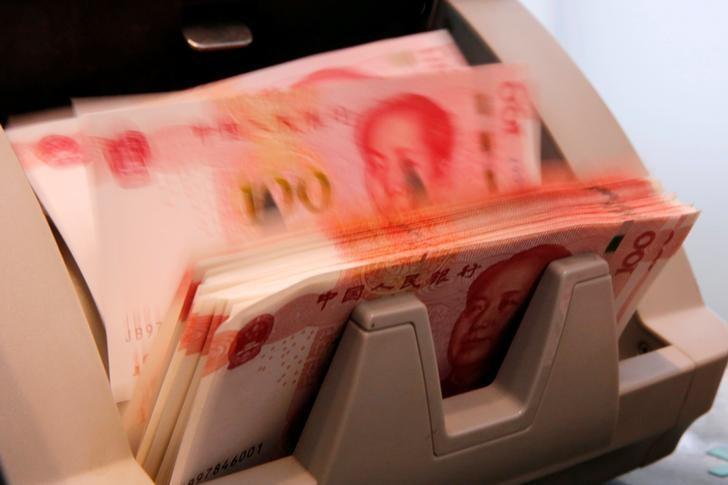 资料图片:2016年3月,北京,一家商业银行的柜员在用点钞机清点人民币纸币。REUTERS/Kim Kyung-Hoon