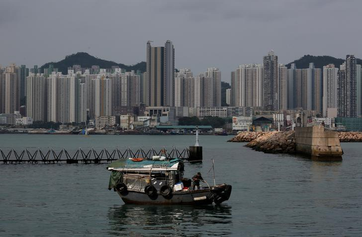 FILE PHOTO: A boat sails in front of private and public housing blocks in Hong Kong, China April 28, 2017.      REUTERS/Bobby Yip/File Photo