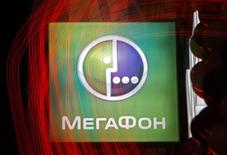 A sign of Russian telecoms group MegaFon hangs outside a shop in St. Petersburg November 27, 2012. Sources said the order book for MegaFon's initial public offering (IPO) would close on Tuesday after being oversubscribed on Monday evening, with the placement likely to be priced in the lower half of the offer range. The red lights reflected in the shop window were taken using long exposure. REUTERS/Alexander Demianchuk (RUSSIA - Tags: BUSINESS TELECOMS)