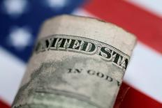 Долларовая купюра на фоне американского флага 1 июня 2017 года.  Доллар торгуется около нуля после публикации слабых инфляционных данных в США, которые заставили инвесторов гадать, продолжит ли ФРС следовать плану повышения ставок в этом году. REUTERS/Thomas White/Illustration