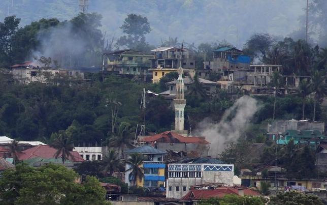 6月15日、フィリピンの政治家は、過激派組織「イスラム国」(IS)系武装勢力と治安当局による激しい戦闘が続いている南部ミンダナオ島のマラウィ市で500─1000人が死亡していると明らかにした。写真は爆撃を受け黒煙が上がるマラウィ市街。(2017年 ロイター/Romeo Ranoco)
