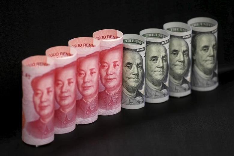 资料图片:2016年1月,百元面值的人民币纸币和美元现钞。REUTERS/Jason Lee