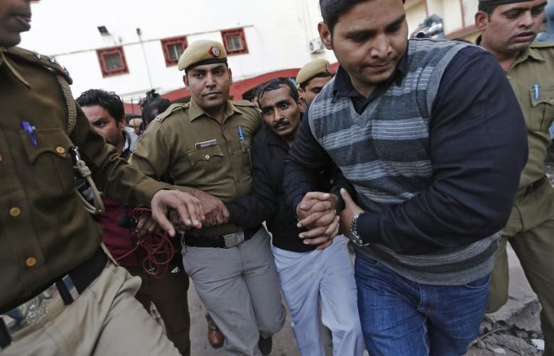 Policemen escort driver Shiv Kumar Yadav (3rd R in black jacket) who is accused of a rape outside a court in New Delhi December 8, 2014. REUTERS/Adnan Abidi