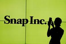 FILE PHOTO: A woman stands in front of the logo of Snap Inc. on the floor of the New York Stock Exchange (NYSE) while waiting for Snap Inc. to post their IPO, in New York City, New York, U.S. on March 2, 2017. REUTERS/Lucas Jackson/File Photo - RTS1686M