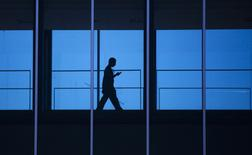 A student uses his mobile phone as he walks in Waterloo April 18, 2012.  REUTERS/Mark Blinch
