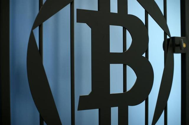 6月16日、岩村充・早稲田大学大学院教授は、ビットコインに追随する他の貨幣ソリューション(アルトコインやデジタル銀行券)が「価値安定」に力を入れていけば、将来的に中銀の通貨発行独占が崩れる可能性もあると指摘。写真はビットコインのロゴを配したドア。仏パリで2014年7月撮影(2017年 ロイター/Benoit Tessier)