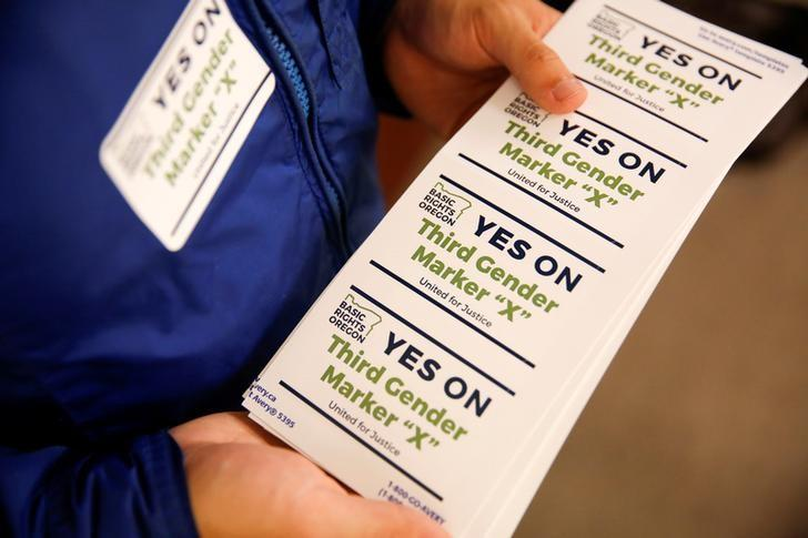 FILE PHOTO: An employee of the advocacy group Basic Rights Oregon hands out stickers during an Oregon Driver and Motor Vehicle department public hearing on the rights of transgender people as the state considers adding a third gender choice to driver's licenses and identification cards, in Portland, Oregon, May 10, 2017. REUTERS/Terray Sylvester/File Photo