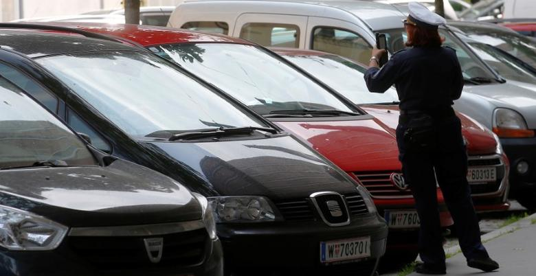 A traffic warden checks cars parked on a street in Vienna, Austria May 31, 2017. REUTERS/Heinz-Peter Bader