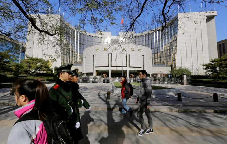 FILE PHOTO: People walk past the headquarters of the People's Bank of China (PBOC), the central bank, as two paramilitary police officials patrol around it in Beijing November 20, 2013.   REUTERS/Jason Lee/File Photo